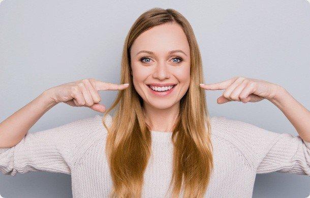 Kobieta wskazuje palcami naswój biały uśmiech